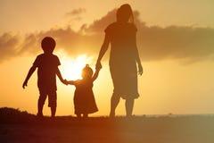 Будьте матерью и 2 дет идя на пляж захода солнца Стоковое Изображение RF