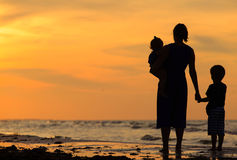 Будьте матерью и 2 дет идя на пляж на заходе солнца Стоковое Изображение