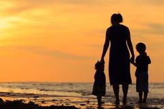 Будьте матерью и 2 дет идя на пляж на заходе солнца Стоковое фото RF