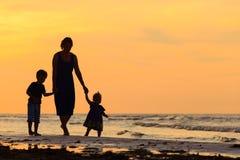 Будьте матерью и 2 дет идя на пляж на заходе солнца Стоковые Фотографии RF