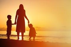 Будьте матерью и 2 дет идя на пляж на заходе солнца Стоковое Изображение RF