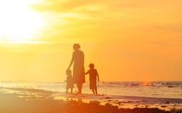 Будьте матерью и 2 дет идя на пляж на заходе солнца Стоковая Фотография