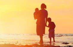 Будьте матерью и 2 дет идя на пляж на заходе солнца Стоковые Фото