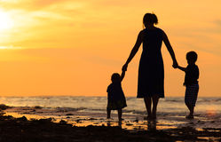 Будьте матерью и 2 дет идя на пляж на заходе солнца Стоковая Фотография RF