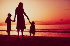 Будьте матерью и 2 дет идя на пляж на заходе солнца Стоковые Изображения