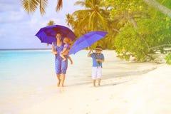 Будьте матерью и 2 дет на пляже с зонтиками Стоковые Изображения