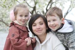 Будьте матерью и 2 дет обнимая среди зацветая сада Стоковое Фото