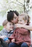 Будьте матерью и 2 дет обнимая среди зацветая сада Стоковое Изображение