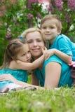 Будьте матерью и 2 дет обнимая среди зеленой травы Стоковое Изображение