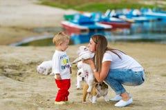 Будьте матерью и маленькая игра сына с щенком на песках на реке Стоковые Фото