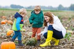 Будьте матерью и 2 маленьких сыновь имея потеху на заплате тыквы. Стоковая Фотография