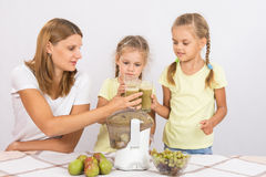 Будьте матерью и 2 дочери постучанной друг против друга с стеклами свеже сделанного сока от груш и виноградин Стоковые Фотографии RF