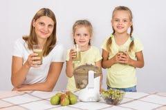 Будьте матерью и 2 дочери с стеклами свеже сделанного сока от груш и виноградин Стоковое фото RF