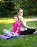 Будьте матерью и усмехаясь йога дочери практикуя и сидеть назад к Стоковое Изображение