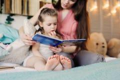 Будьте матерью книги чтения к дочери малыша в спальне на спокойная ночь Стоковые Фотографии RF