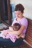 Будьте матерью кормить ее маленького младенца грудью на патио Стоковая Фотография