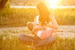 Будьте матерью кормя грудью младенца в солнечном свете на заходе солнца Стоковые Фотографии RF