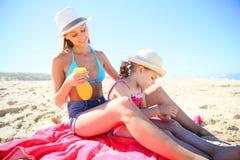 Будьте матерью класть солнцезащитный крем дальше назад ее дочери Стоковое Изображение RF