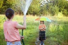 Будьте матерью мочить ее сына при зонтик шланга играя в дожде Стоковые Изображения RF