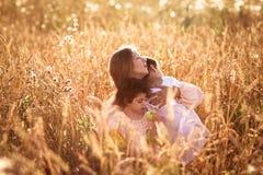 Будьте матерью обнимать ее сына и дочери в пшеничном поле Стоковая Фотография
