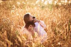 Будьте матерью обнимать ее сына и дочери в пшеничном поле Стоковые Фото