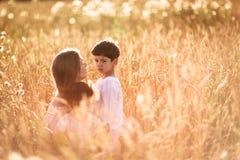 Будьте матерью обнимать ее сына и дочери в пшеничном поле Стоковое фото RF