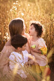 Будьте матерью обнимать ее сына и дочери в пшеничном поле Стоковое Изображение