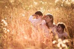 Будьте матерью обнимать ее сына и дочери в пшеничном поле Стоковые Фотографии RF