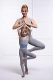Будьте матерью дочери делая тренировку йоги, фитнес, спортзал нося такие же удобные tracksuits, спорт семьи, спаренные спорт Стоковое фото RF