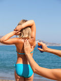 Будьте матерью прикладывать солнцезащитный крем к ее ребенку на пляже Стоковые Изображения