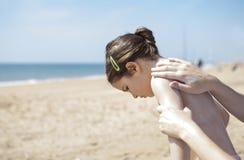 Будьте матерью прикладывать сливк sunblock к ее задней части дочери дальше Стоковые Изображения RF
