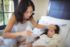 Будьте матерью проверять температуру тела больной дочери в комнате кровати Стоковые Изображения