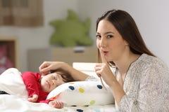Будьте матерью просить безмолвие с ее спать малыша стоковые изображения rf