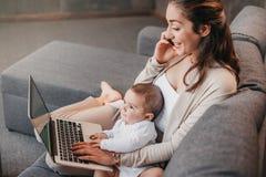 Будьте матерью работы от дома, говоря на smartphone пока тратящ время с ее ребёнком стоковое изображение
