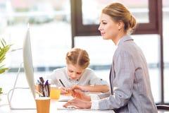 Будьте матерью работы с компьютером пока ее чертеж дочери в офисе Стоковые Изображения RF