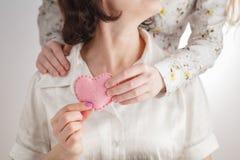 Будьте матерью рук ` s и руки ` s ребенка держа красное сердце совместно Стоковое фото RF