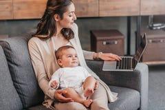 Будьте матерью сидеть на кресле с ее сыном и использовать компьтер-книжку дома Стоковое Изображение RF