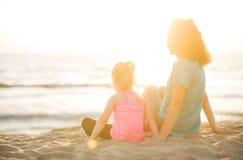 Будьте матерью усмехаться над плечом сидя рядом с дочерью на пляже Стоковое Изображение RF