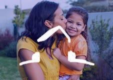 Будьте матерью целовать ее дочь против плана дома в предпосылке Стоковые Фото