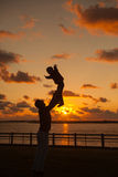 Будьте отцом бросать его ребенк вверх в воздухе на пляже, силуэте s Стоковые Фотографии RF