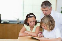 Будьте отцом вместе с дет и таблеткой в кухне Стоковые Изображения RF