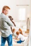 Будьте отцом держать щенка retriever labrador, счастливой семьи позади дома Стоковая Фотография