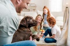 Будьте отцом держать щенка retriever labrador, счастливой семьи позади дома Стоковые Фотографии RF