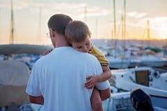 Будьте отцом, держащ его маленький ребенка, пока спящ, наслаждаясь su Стоковые Фото