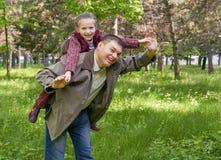Будьте отцом играть с девушкой ребенка в парке лета, солнечном свете, зеленой траве и деревьях Стоковые Изображения RF