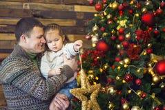 Будьте отцом и его маленькая дочь украшая рождественскую елку на стоковые изображения rf