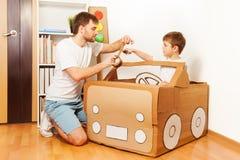 Будьте отцом и его сын делая автомобиль игрушки из картонной коробки Стоковая Фотография RF