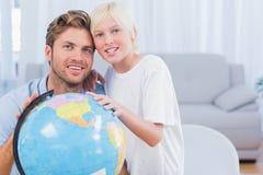 Будьте отцом и его сын смотря глобус и усмехаться Стоковые Фотографии RF