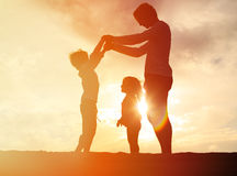 Будьте отцом и 2 дет играя на небе захода солнца Стоковое Фото