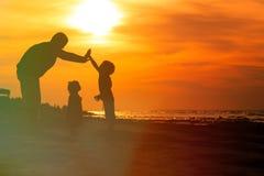 Будьте отцом и 2 дет играя на пляже захода солнца Стоковая Фотография